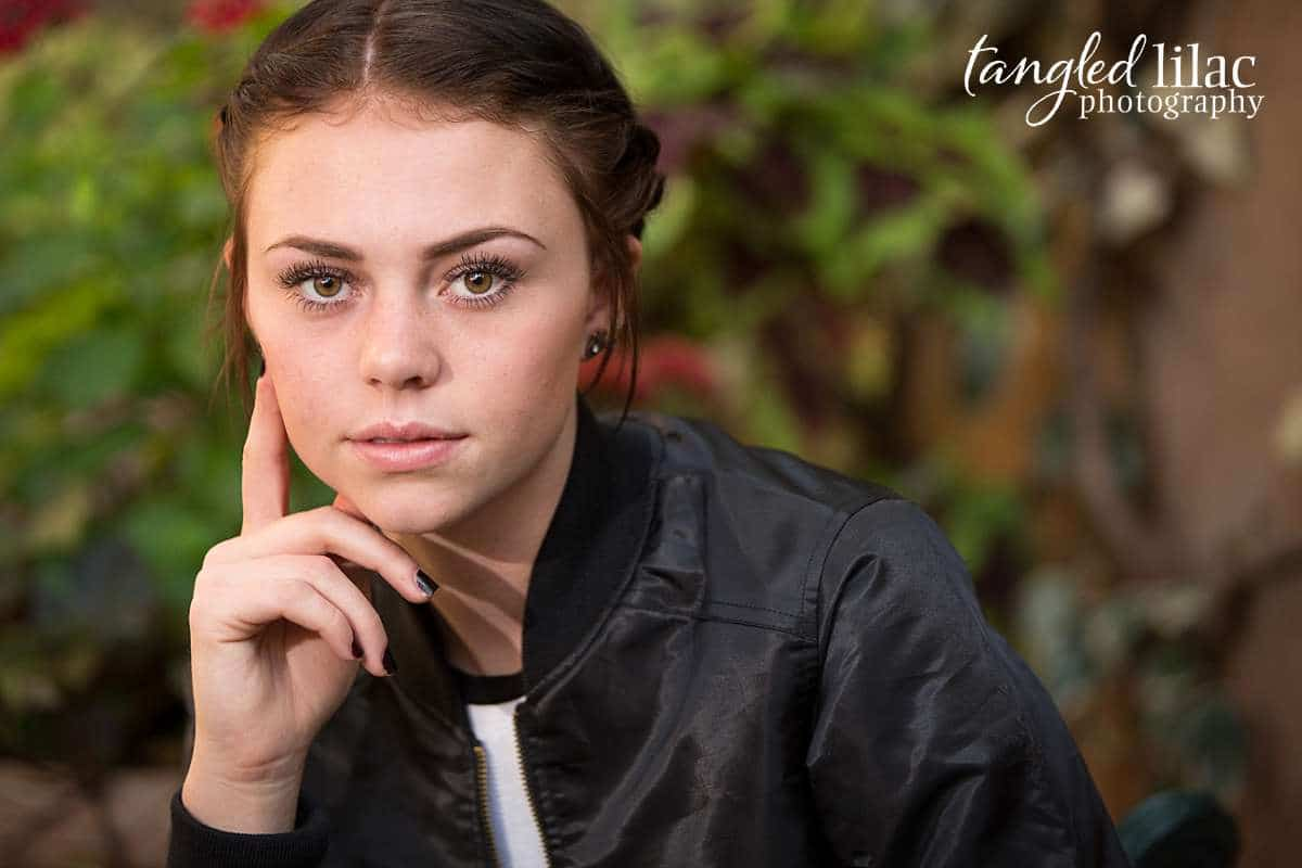 Serious and glamorous high school senior in a satin jacket and minimal makeup striking a vogue pose with minimal make up Image by High School Senior Photographer Melissa Dunstan in Los Angeles California