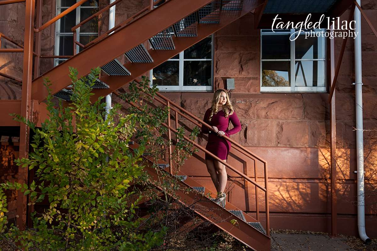 College Senior on a staircase wearing a red dress with off camera flash