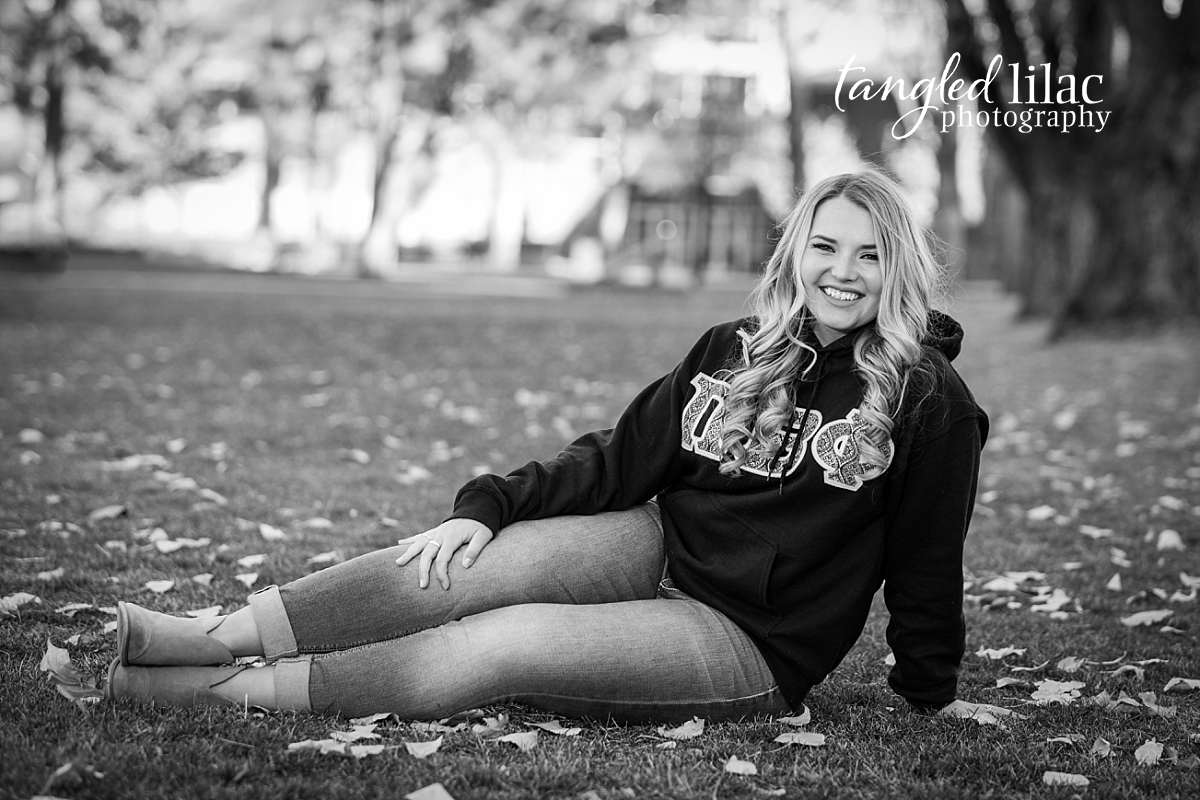 Pi Beta Phi College Student wearing a sweater on a lawn with leaves
