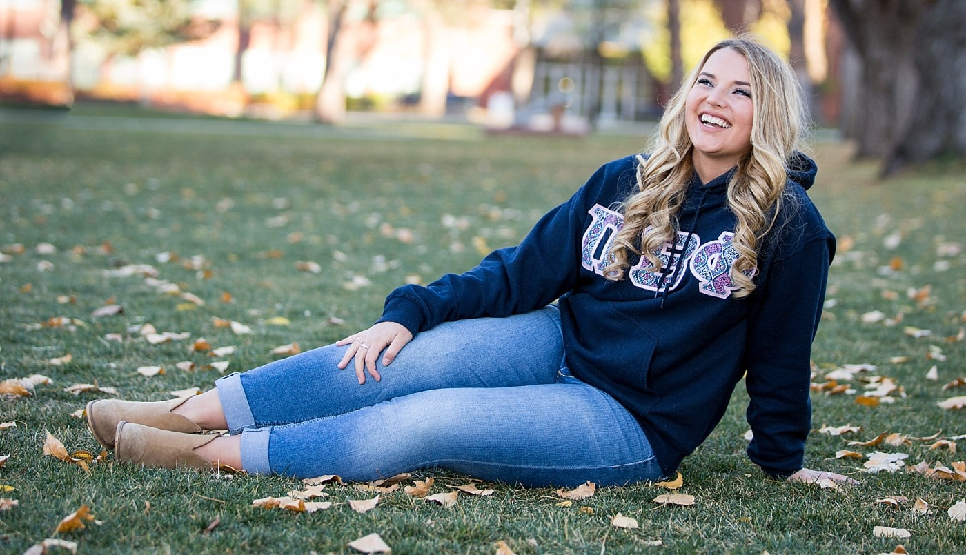 University Senior during her graduation photos in her Pi Beta Phi Sweatshirt on the lawn of Northern Arizona University