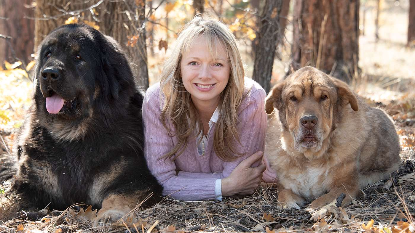Los Angeles Pet and Headshot Photographer with her dogs a Tibetan Mastiff and Reservation Dog in the forest during the fall with fall colors under an oak tree