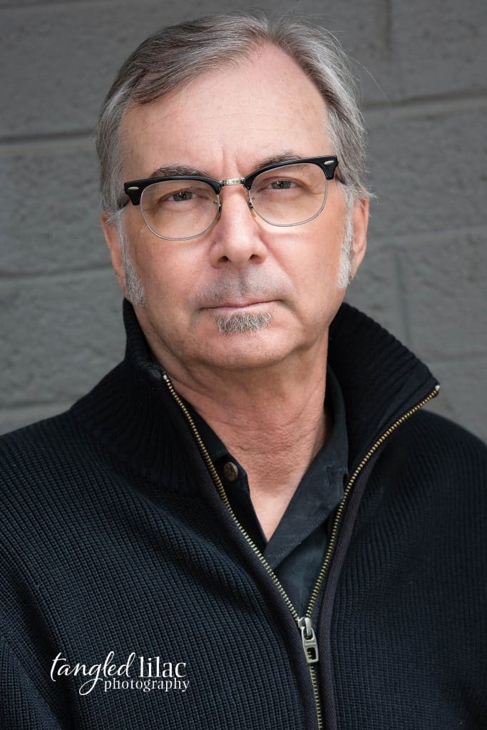 Flagstaff Headshot of Professor of English on grey background with a black sweater and glasses